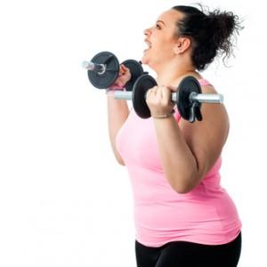 Eine übergewichtige Frau trainiert freudig mit Hanteln