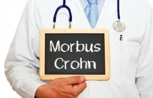Ausschnitt eines Oberkörpers eines Arztes mit einerTafel mit der Aufschrift Morbus Crohn